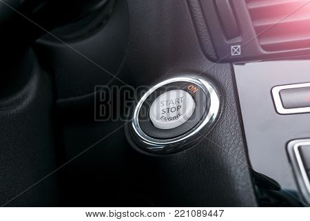Car dashboard with focus on engine start stop button, Modern car interior details. Start/stop. Soft lightning