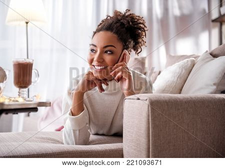 Portrait of dreamful african woman communicating by cellphone at home. She is relaxing on sofa and smiling. Home coziness concept