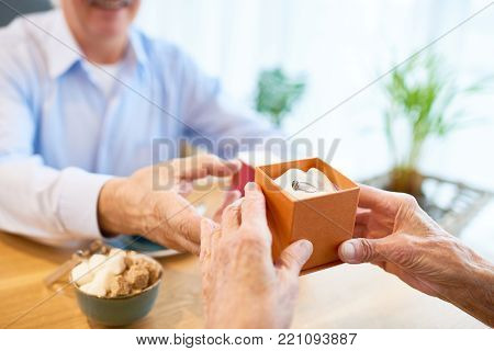 Close-up shot of senior man wearing blue shirt sitting at restaurant table with gift box containing ring and making proposal to his soulmate, blurred background
