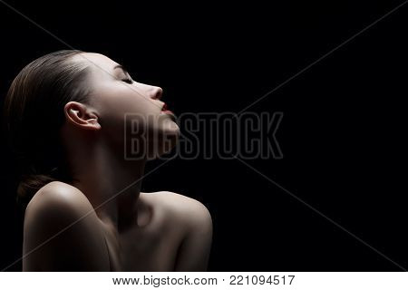 sensual aroused woman with closed eyes on black background