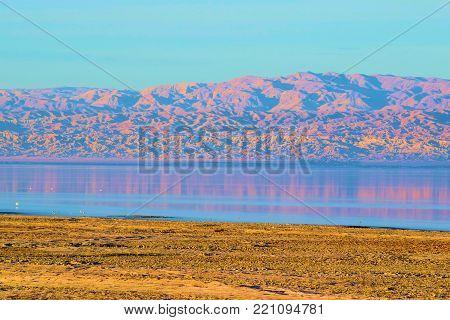Rural plain with a lake and barren mountains beyond taken at the Salton Sea, CA