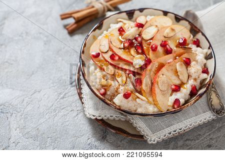 Coconut rice with pomegranate, pear, cinnamon and almond slices