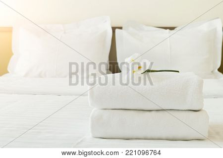 Stack of towels and flower on bed in hotel room. White orchid as welcome gesture, room service, accommodation concept, copy space