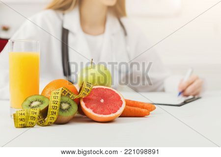 Nutritionist desk with healthy fruits, juice and measuring tape. Dietitian working on diet plan. Weight loss and right nutrition concept