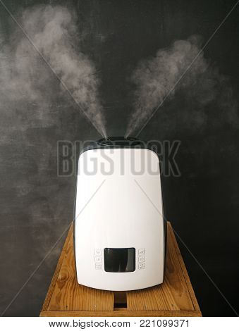 ultrasonic digital humidifier distributes steam in the living room against a blackboard background.