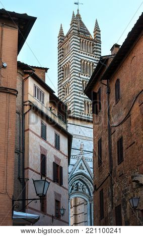 Siena Cathedral (Duomo di Siena) bell tower view from street. Siena is italian medieval town, capital of Siena province, Tuscany, Italy. Historic centre is UNESCO World Heritage Site.