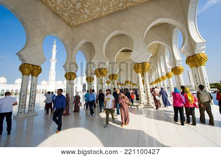 ABU DHABI, UNITED ARAB EMIRATES - DEC 28, 2017: Moslims and tourists are visiting the Sheikh Zayed Mosque in Abu Dhabi. It is the largest mosque in the country.