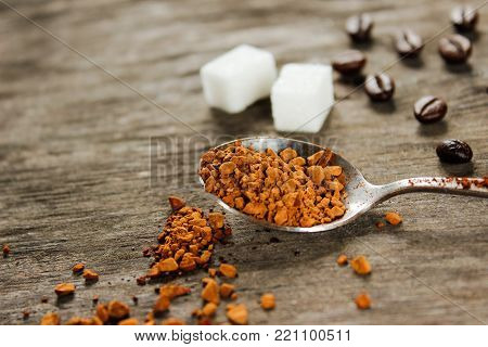 Coffee beans and instant coffee, white square sugar on a wooden table. Side view