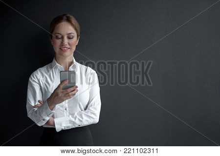 Portrait of smiling businesswoman typing in phone. Labor and technology concept. Copy space