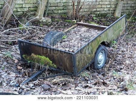 abandoned derelict farming trailer covered in moss and dead leaves