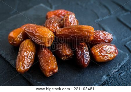 Dried date on black stone background. Heap of dates close up. Healthy snack.
