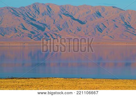 Rural desolate landscape including a lake with barren mountains beyond during sunset taken at the Salton Sea, CA