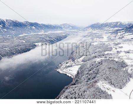 Snow covered winter landscape, cloud over a large lake.