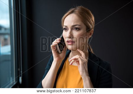 Portrait of disturbed woman telling by phone in modern room. Communication and labor concept