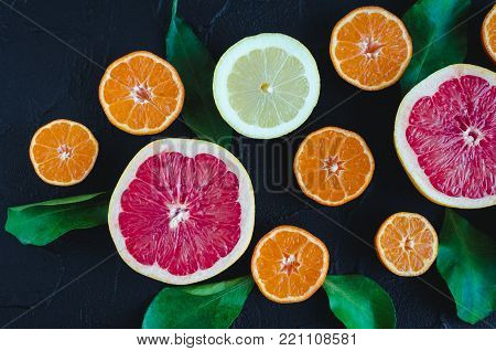 Mixed citrus background. Assorted fresh citrus fruits with leaves on black stone table. Lemon, grapefruit, mandarin. Harvest concept. Healthy eating, dieting. Top view.