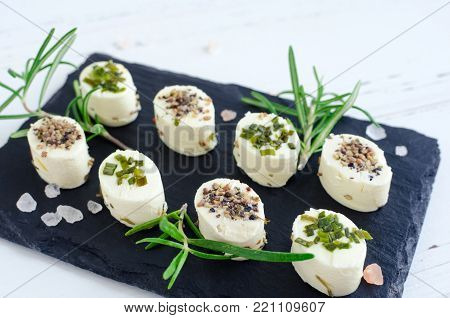 Mini appetizers bocconcini freschi from soft cheese with spices on dark stone board on white wooden background. Italian cuisine.
