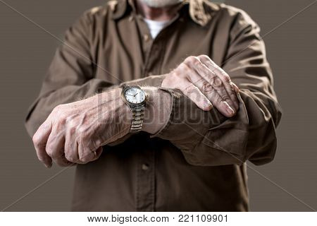 Man checking time on his wristwatch while showing it to camera. Isolated on grey background. Close up