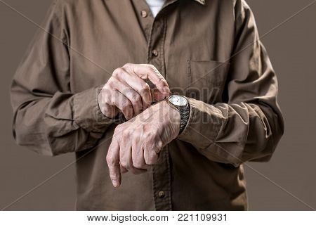 Senior arms pointing at the wristlet antique watch. Isolated on grey background. Close up