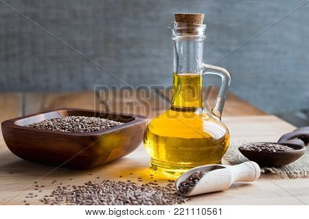 A bottle of flax seed oil on a wooden table, with flax seeds in the foreground