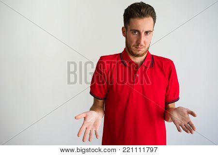 Portrait of ignorant young Caucasian man wearing red t-shirt looking at camera and shrugging shoulders. Ignorance and confusion concept