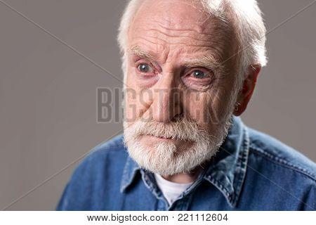 Portrait of meditative gaffer standing at gaze. Isolated on grey background