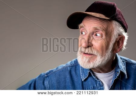 Portrait of gray haired oldster in cap looking aside with interest. Copy space in left side. Isolated on grey background