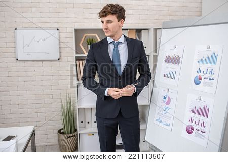 Portrait of young successful businessman standing by whiteboard giving presentation of statistics report on marketing and finance during training seminar, copy space