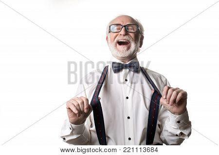 Waist up portrait of joyful old male pulling away his suspenders and laughing. Isolated on background