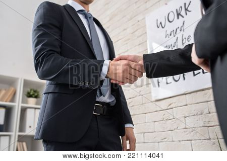 Low angle close up of two successful business people shaking hands in office after finalizing deal