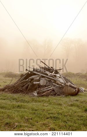 Ancient barn collapsing into a heap with fog obscuring the background.