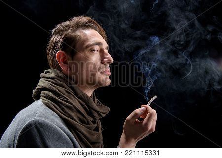 Melancholy. Side view profile of unhappy young elegant man is standing with cigarette. He is looking aside thoughtfully while being in cloud of white smoke. Isolated background