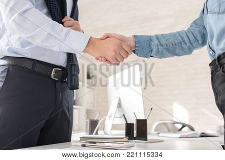 Side view close up of two unrecognizable business people shaking hands with partner in office after finalizing business deal