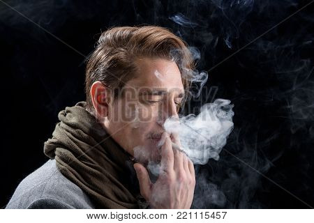 Creative process. Side view of dreamily young trendy man is standing and enjoying bad habit. He is looking down thoughtfully while being in cloud of white smoke. Isolated on dark background