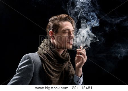 Sadness. Side view of pensive young stylish man is standing and enjoying cigarette. He is looking aside wistfully while being in cloud of smoke. Isolated background