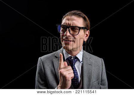 Portrait of irritated young businessman in suit is standing and pointing finger up. He is frowning while looking aside with annoyance. Isolated on dark background