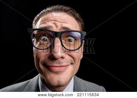 Confused. Close-up portrait of young businessman in glasses is looking at camera embarrassedly. Isolated on dark background