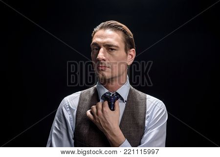 Smart and successful. Portrait of stylish young businessman is standing and looking at camera confidently while adjusting his tie. He is expressing assertiveness. Isolated background