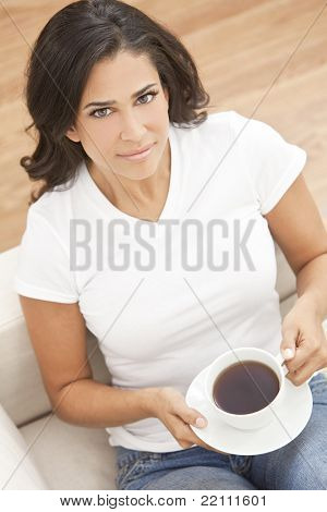 A beautiful young Latina Hispanic woman or girl with an enigmatic smile drinking tea or coffee from a white cup at home on her sofa