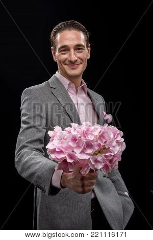 For you. Young pleasant positive man is standing and keeping huge beautiful bouquet. He is looking at camera with charming smile while keeping one hand in pocket of his pants. Isolated