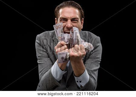 Passion about money. Portrait of adult crazy manager is standing and squeezing dollars in his fists while looking at camera with obsess. Isolated background