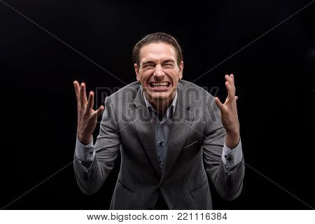 Full of anger. Portrait of annoyed young man is standing with closed eyes while gesticulating madly and feeling aggression. Isolated background