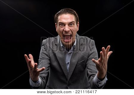 Feeling destroyed. Portrait of angry businessman is shouting and expressing negative emotions while looking at camera with rage. He is gesticulating madly. Isolated background