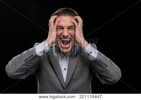 How is it possible. Portrait of angry young man is standing and touching his head. He is looking at camera while expressing annoyed and screaming. Isolated on dark background