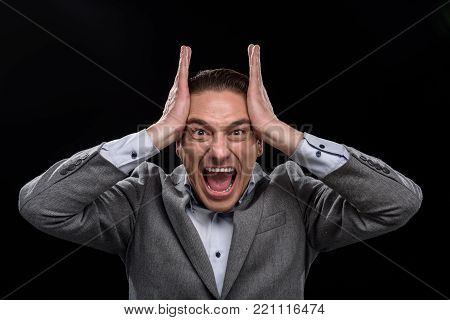 Full of rage. Portrait of annoyed angry young businessman is expressing discontent and shouting loud while touching his head and looking at camera in wide-eyed. Isolated background