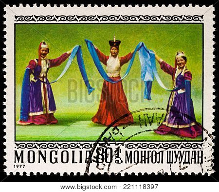 Moscow, Russia - January 08, 2018: A stamp printed in Mongolia, shows three dancing women in traditional Mongolian costumes, series
