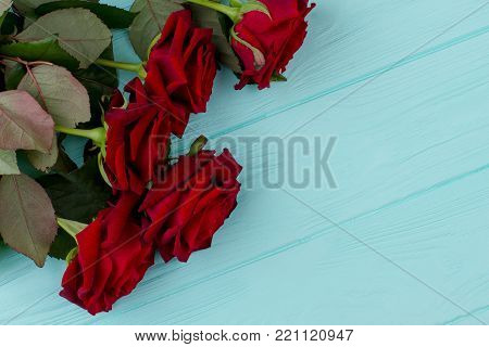 Saint Valentine Day wooden background. Red Valentine Day roses on blue wooden background. Symbolic of love and romance. Space for greeting text.
