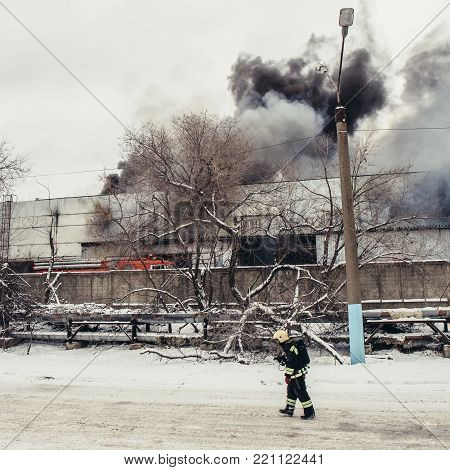 Fireman going left at burning industrial building with fire flames and black smoke background, toned