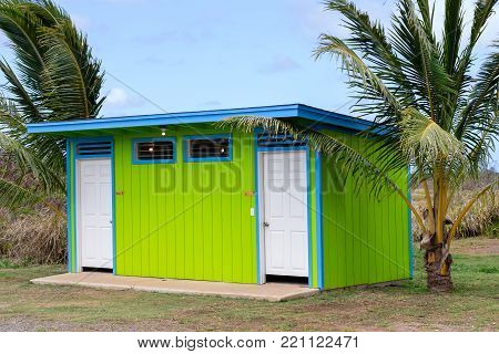 Colorful neat clean green public restroom facility flanked by tropical palm trees in a park on Oahu, Hawaii with signs and doors for men and women