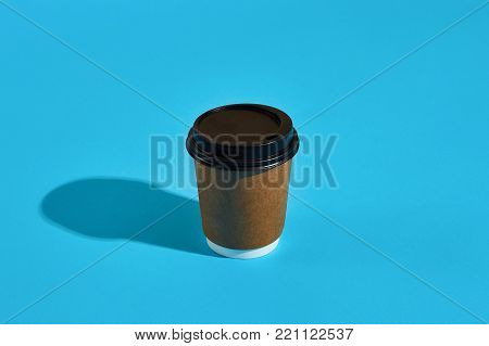 Hot coffee in brown paper cup with black lid on blue background with shadow, blurred and soft focus image. Still life. Copy space
