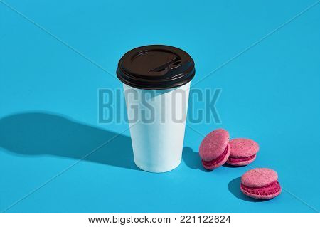 Hot coffee in white paper cup with black lid and pink macaroons on blue background with shadow, blurred and soft focus image. Still life. Copy space